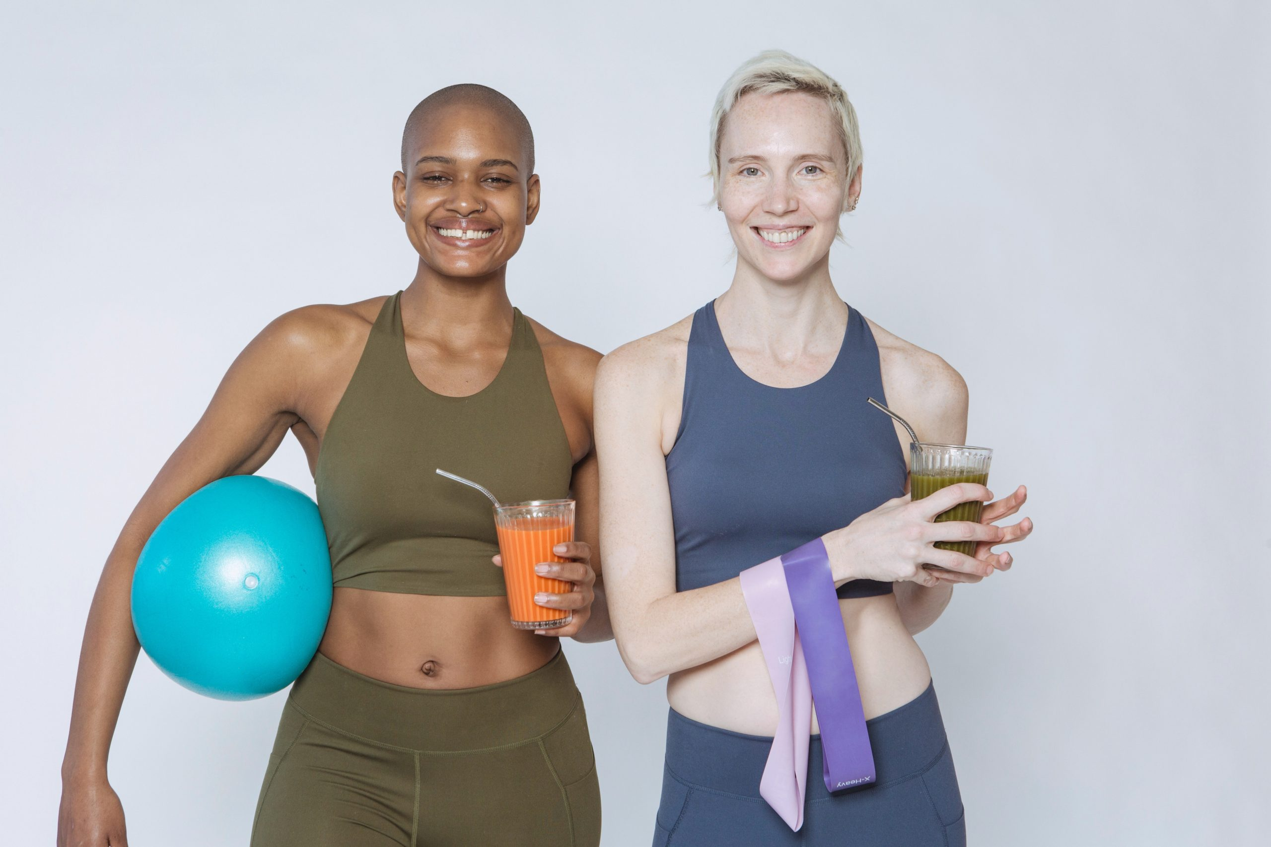 two women in workout clothing with a ball and resistance band
